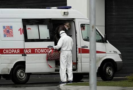 Kasvonaamiota pitävä nainen poistuu ambulanssista tiistaina koronaviruspotilaille varatun sairaalan edessä.