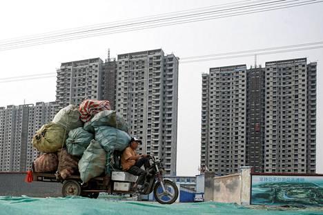 Kierrätysmateriaalia kuskaava moottoripyöräilijä ajaa rakenteilla olevan kerrostaloalueen ohi Pekingissä tiistaina.