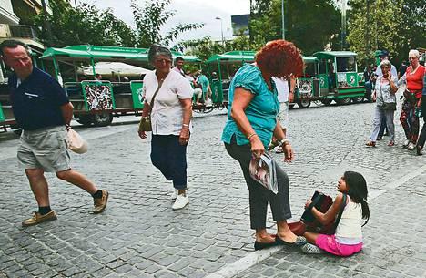 Kaupan omistaja hätisteli haitaria soittavaa romanilasta kävelytieltä Ateenan keskustassa syyskuussa. Kreikka on yrittänyt auttaa katulapsia pois kaduilta. Useimmat katulapset ovat romaneja.