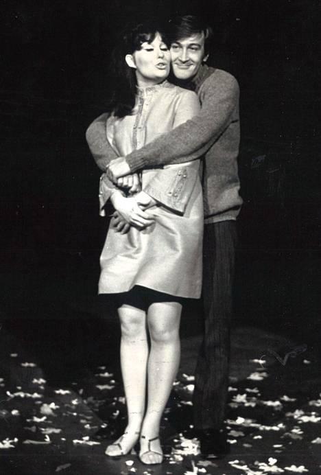 """Laila Kinnusen ja Ville-Veikko Salmisen yllätämme kaulakkain ohjelmassa Kolumbus, joka on ennakkotietojen mukaan """"vapaasti mukaeltu viihdemuistelma eräältä purjehdukselta"""". Ohjaus on myös Ville-Veikko Salmisen. – Tv-1 20.15."""
