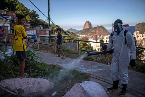 Vapaaehtoistyöntekijä desinfioi ympäristöä Santa Martan favelassa Rio de Janeirossa maanantaina. Taustalla siintää kaupungin kuuluisa Sokeritoppavuori.