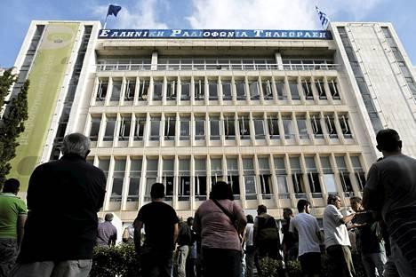 Ihmiset seisoivat Kreikan yleisradion ERT:n pääkonttorin edessä hallituksen kerrottua ERT:n sulkemisesta tiistaina.