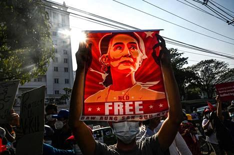 Mielenosoittaja piteli Myanmarin entisen johtajan Aung San Suu Kyin kuvaa mielenosoituksessa Yangonissa helmikuussa.
