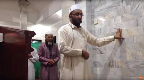 Sosiaalisessa mediassa levinneellä videolla näkyy, miten imaami jatkaa rukoustaan vain toisella kädellä seinästä kiinni pitäen.