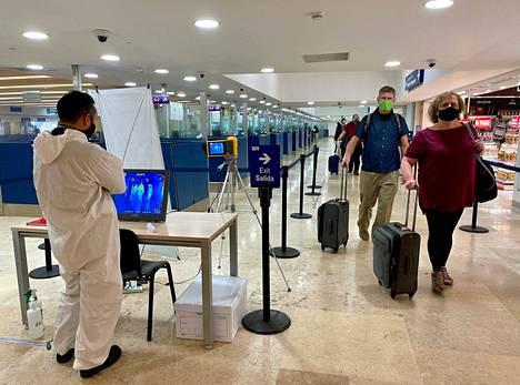 Matkustajat ohittavat Cancúnin lentokentällä Meksikossa kuumetta mittaavan laitteen, jolla yritetään seuloa matkustajista koronavirustartunnan saaneet.