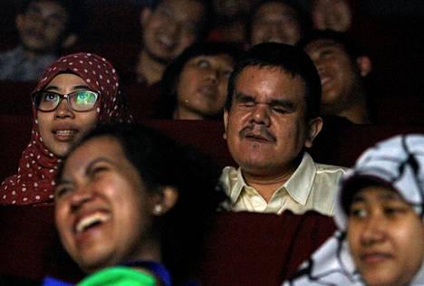 Vapaahtoisavustaja Prasetyaning Diah (vas.) selostaa elokuvan tapahtumia Siswantolle näkövammaisille järjestetyssä elokuvanäytöksessä Jakartassa Indonesiassa.