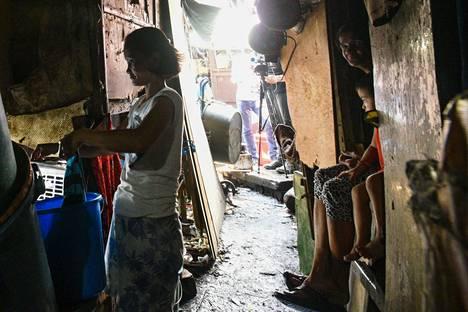 Nainen pesi pyykkiä perheensä katsellessa vierestä keskiviikkona Filippiinien pääkaupungissa Manilassa, jonka asukkaat on määrätty pysymään kotona.