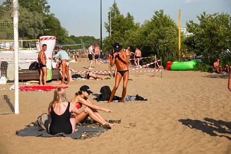 Pietarilaisia viettämässä kesäkuussa hellepäivää yksityisellä rannalla Krestovskin saarella.