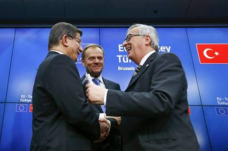 Turkin pääministeri Ahmet Davutoglu (vas.), Eurooppa-neuvoston puheenjohtaja Donald Tusk ja Euroopan komission puheenjohtaja Jean Claude Juncker tervehtivät toisiaan EU-huippukokouksessa Brysselissä maanantaina.