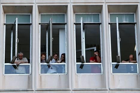 Henkilökuntaa Kreikan valtiollisen TV-ja radiotoimitalon ERT:n ikkunopissa eilen Ateenassa.