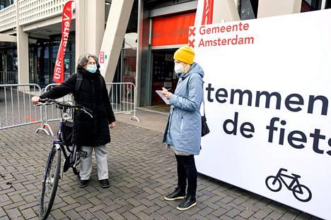 Brysselin-kirjeenvaihtaja Jenni Virtanen (oik.) haastatteli äänestäjä Iris Maheria Amsterdamissa maaliskuussa. Hollannin vaaleissa oli koronapandemian vuoksi mahdollista äänestää pyörän selästä tai autonsa kyydistä.