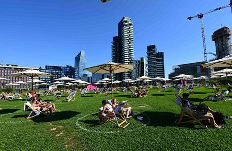 Ihmiset ottivat aurinkoa puistossa Milanon keskustassa kesäkuun lopussa.