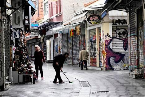 Mies lakaisi katua kauppansa edessä aikaisin aamulla, ennen kauppojen aukeamista, Monastirakin alueella Ateenassa helmikuussa.