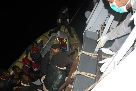 Italian merivoimien pelastajat auttoivat pakolaisia kiipeämään laivaan lähellä Italian Pozzallon satamaa tiistaiyönä.
