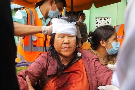 Loukkaantunutta mielenosoittajaa hoidettiin Myanmarin Mandalayssa lauantaina.
