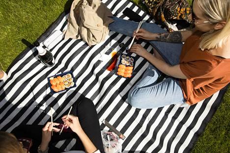 Caroline Eerola (vas.) ja Riina Mutikainen nauttivat sushia ja kuohuviiniä Esplanadin puistossa.