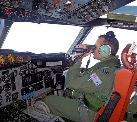 Australian ilmavoimien maanantaina julkaisemassa kuvassa AP-3C Orion -vartiokoneen lentäjä tarkkailee merenpintaa Malesiassa kadonneen lentokoneen etsintäoperaatiossa.