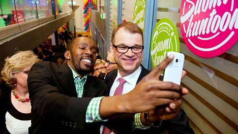 Kampanjatyöntekijä Josiah Mutiti otti selfien Juha Sipilän kanssa keskustan puoluetoimiston vaalivalvojaisissa huhtikuussa 2015.