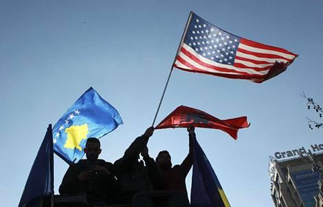 Ihmiset juhlivat Kosovon, Albanian ja Yhdysvaltojen lippujen kera Kosovon itsenäisyysjulistuksen kymmenvuotispäivänä Pristinassa viime helmikuussa.