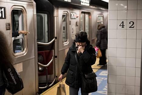 New Yorkin metrossa ihmiset suojaavat kasvojaan kaulaliinoillaan ja välttelevät kontaktia muiden kanssa.