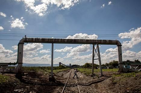 Photsanengin kylää reunustavat rautatie sekä kaivosyhtiöön johtavat putket ja voimalinjat. Kylässä (kuvassa oikealla) eletään yhä hökkeleissä, joissa vain harvoilla on oma vesipiste.