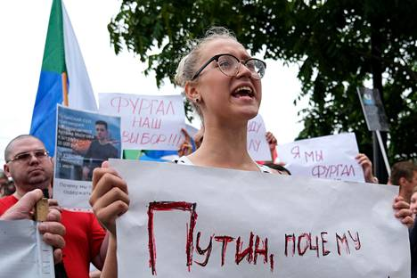 """The woman took part in the protest, holding a sign that reads """"Putin, why""""."""