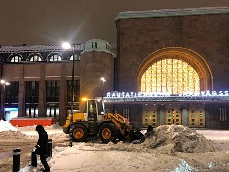 Auratraktori kasasi Helsingin Asema-aukiolle kertynyttä lunta varhain torstaiaamuna.