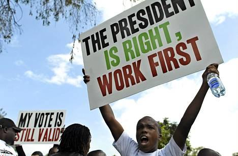 Kenialaiset osoittivat mieltään parlamentin palkankorotusaikeita vastaan Nairobissa toukokuun puolessavälissä. Kyltin teksti kertoo: Presidentti on oikeassa, tehkää ensin töitä.