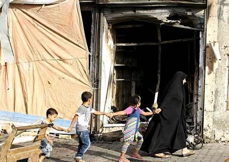 Irakilaisperhe kävelee autopommin aiheuttamien tuhojen ohitse Bagdadissa.