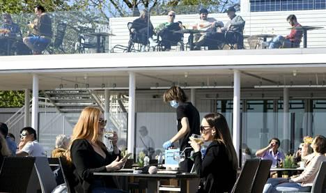 Ihmiset nauttivat auringosta Cafe Caruselin terassilla Helsingin Kaivopuistossa lauantaina 29. toukokuuta 2021.