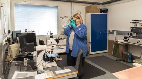 Johanna Turunen tarkasti poikkileikkauskuvaa piirilevystä Aspocompin Oulun-tehtaalla perjantaina.