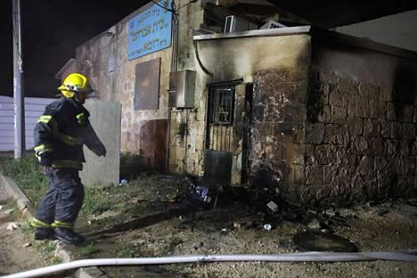 Palomies tarkasti poltettua synagogaa Lodissa perjantaina.