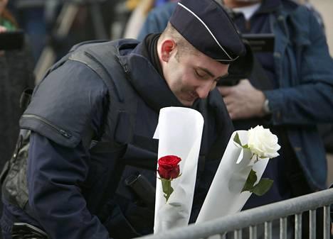 Poliisimies toi kukkia Bataclanin konserttisalin edustalle.