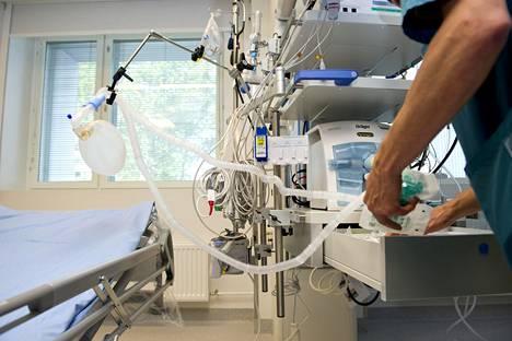 Sairaanhoitaja käsittelee hengityskonetta Meilahden sairaalan tehohoito-osastolla Helsingissä.