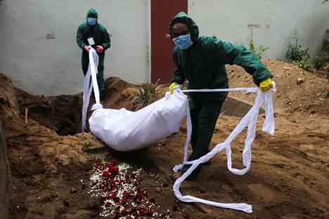 Vapaaehtoiset kantoivat koronavirukseen kuolleen ruumista Mumbaissa Intiassa.