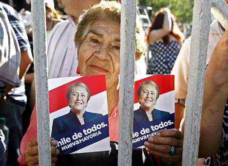Kannattaja juhli Michelle Bacheletin sosialistipuolueen toimiston edustalla sunnuntaina. Alustavien tulosten mukaan Bachelet palaa johtamaan maata.