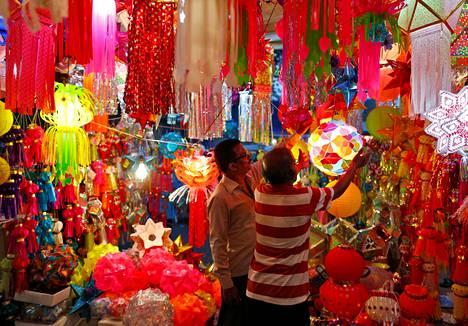 Kauppiaat ripustivat lyhtyjä myytäväksi kauppakadulla Mumbaissa Intiassa diwali-juhlan alla viime sunnuntaina. Diwali on valon juhla.