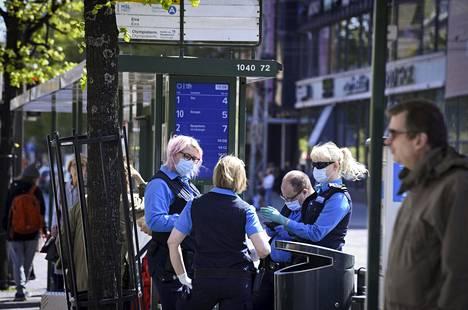 Kasvomaskein suojautuneita HSL:n lipuntarkastajia raitiovaunupysäkillä Lasipalatsin edessä Helsingissä 27. toukokuuta.