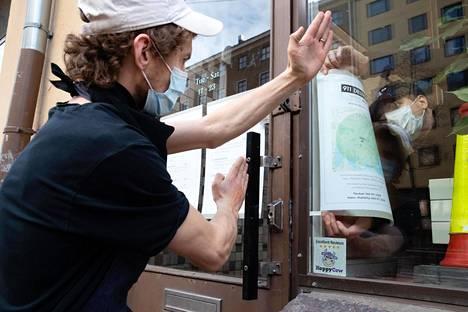 Ravintoloitsija Ossi Paloneva katsoo ulkona, kun suunnittelija Erwin Laiho laittaa ilmoitusta kotiinkuljetusalueesta ravintola Villdin ikkunaan.