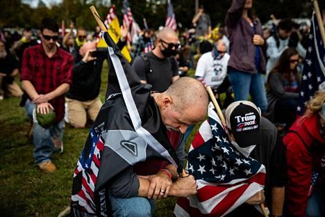 Proud Boys -ryhmän jäseniä polvistui rukoukseen Portlandin Delta Parkissa järjestetyssä kokoontumisessa perjantaina.