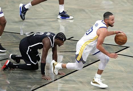 Golden State Warriorsin Stephen Curry kuljetti palloa ottelussa Brooklyn Netsiä vastaan Caris LeVertin katsoessa tilannetta kentän pinnasta.