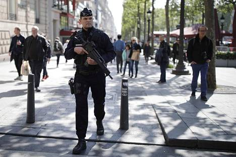 Poliisi partioi jalankulkijoiden joukossa Champs Elysees´llä perjantaina.