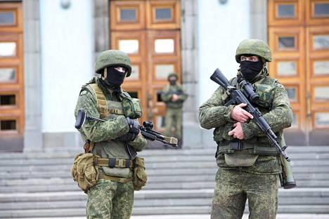 Merkittömiin taisteluvarusteisiin sonnustautuneet sotilaat vartioivat Krimin hallintorakennusta Simferopolissa 1. maaliskuuta 2014. Tunnuksettomista sotilaista tuli hybridisodankäynnin symboli.
