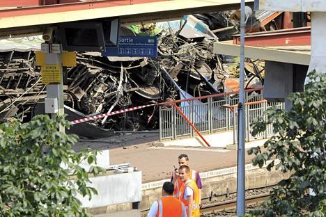 Ranskan valtiollisen rautatieyhtiön SNCF:n työntekijät seisoivat Bretigny-sur-Orgen juna-asemalla lauantaina. Kaukoliikenteen juna oli perjantaina matkalla Pariisista kohti Limogesin kaupunkia Keski-Ranskassa, kun se ratavian vuoksi ajautui raiteilta.