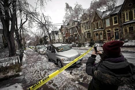 Nainen ottaa valokuvaa auton konepellille pudonneesta jäisestä oksasta Torontossa sunnuntaina.