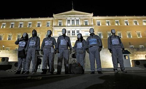 Vanginvaatteisiin pukeutuneet mielenosoittajat vastustivat säästötoimia Kreikan parlamenttitalon edustalla tiistaina.