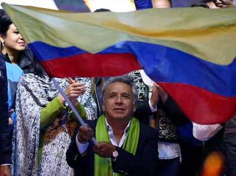 Vasemmiston ehdokas Lenín Moreno heilutti Ecuadorin lippua odottaessaan presidentinvaalien toisen kierroksen tuloksia Quitossa sunnuntaina. Moreno istuu pyörätuolissa. Hänen jalkansa halvaantuivat 1990-luvun lopulla, kun häntä ammuttiin ryöstön yhteydessä.