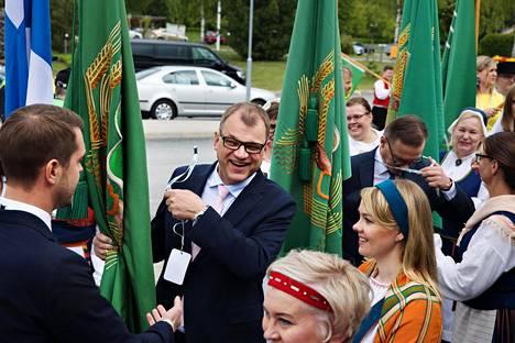 Juha Sipilä ja Katri Kulmuni valmistautuivat perjantaina puoluekokouksen aloittavaan lippumarssiin Katinkullan pihalla.