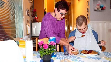 Raija Kopra tarjoilee aikuiselle pojalleen Olli Kopralle ruokaa kotonaan Järvenpäässä.