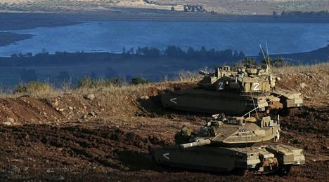 Israelin panssarivaunut olivat maanantaina asemissa Golanin kukkuloilla. Vastarannalla näkyvä kylä on Syyriaa.